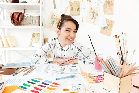 Photo of young happy woman fashion illustrator sitting at the table and drawing. Looking at camera. Stock fotó