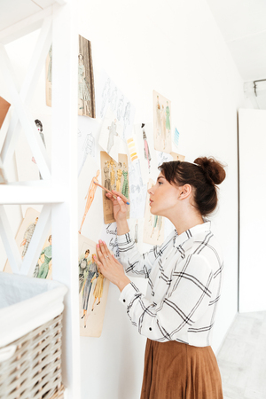 Picture of young concentrated lady fashion illustrator standing near a lot of illustrations and drawing. Looking aside.