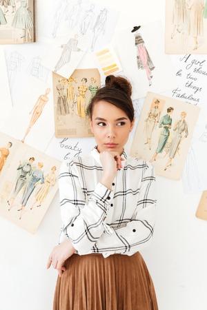 젊은 심각한 생각 여자 패션 삽화가 삽화를 많이 근처에 서의 이미지. 옆으로보고.