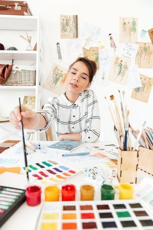 그림 젊은 집중된 여자 패션 일러스트 레이 터 테이블 및 드로잉에 앉아. 옆으로보고. 스톡 콘텐츠