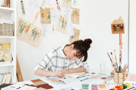 꽤 젊은 집중된 여자 패션 삽화가 테이블 및 그리기 앉아 이미지. 옆으로보고.