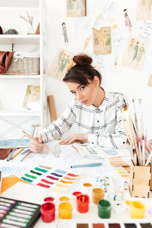 Image of young serious woman fashion illustrator sitting at the table and drawing. Looking at camera.