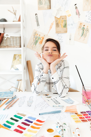 joking: Image of young funny lady fashion illustrator sitting at the table and joking holding pencil with lips. Looking at camera. Stock Photo