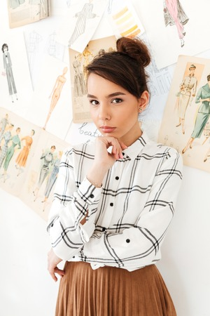 Picture of young concentrated thinking woman fashion illustrator standing near a lot of illustrations. Looking at camera.