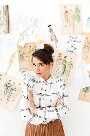 Picture of young pretty woman fashion illustrator standing near a lot of illustrations. Looking at camera with arms crossed.