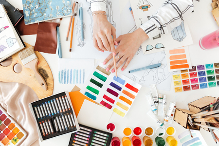 Top view of a female fashion designer working on sketches with paint on her workplace Stock Photo