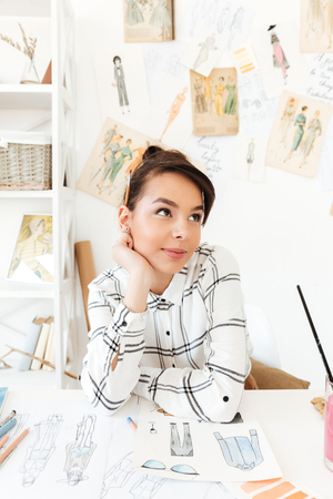 looking aside: Photo of young pretty thinking woman fashion illustrator sitting at the table and drawing. Looking aside. Stock Photo