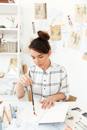looking aside: Photo of young concentrated woman fashion illustrator sitting at the table and drawing. Looking aside.
