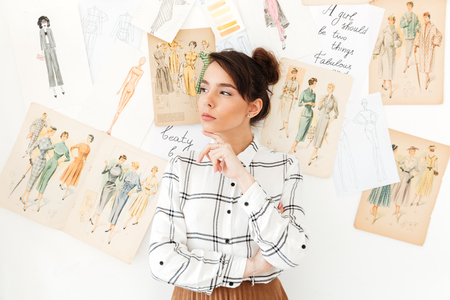 Image of young serious thinking woman fashion illustrator standing near a lot of illustrations. Looking aside.