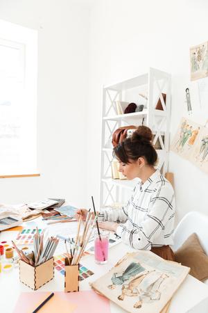 젊은 집중된 여자 패션 삽화가 테이블 및 그리기 앉아 이미지. 옆으로보고.