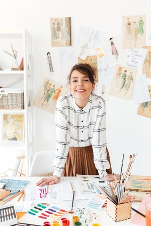Happy stylish woman fashion designer standing at her workplace in studio