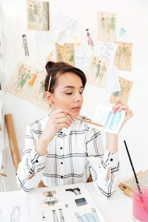 Image of young concentrated woman fashion illustrator sitting at the table. Looking aside.