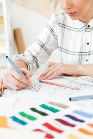 Cropped picture of young woman fashion illustrator sitting at the table and drawing.