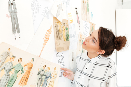 Image of young happy lady fashion illustrator standing near a lot of illustrations and looking at them. Фото со стока