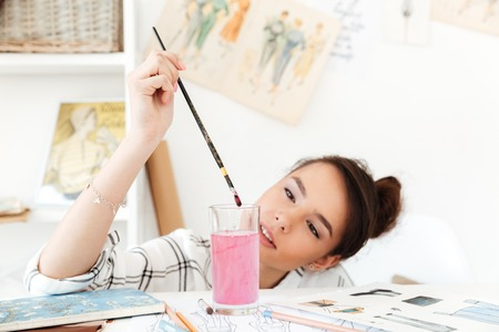 Image of young serious woman fashion illustrator sitting at the table and drawing. Looking aside. Stock Photo - 80195344