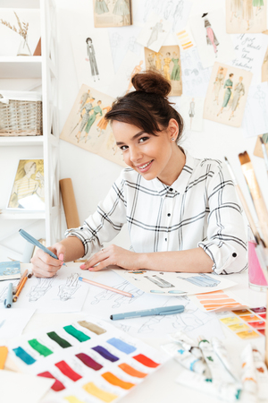Photo of young happy woman fashion illustrator sitting at the table and drawing. Looking at camera. Stock Photo - 80195342