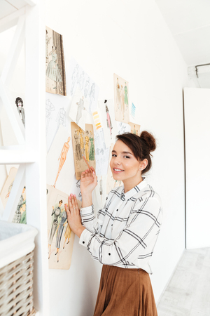 Image of young happy woman fashion illustrator standing near a lot of illustrations and drawing. Looking at camera.