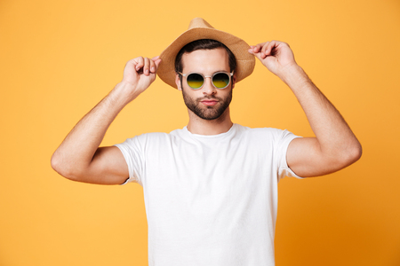 concentrate: Image of concentrated young man standing isolated over yellow background. Looking at camera.