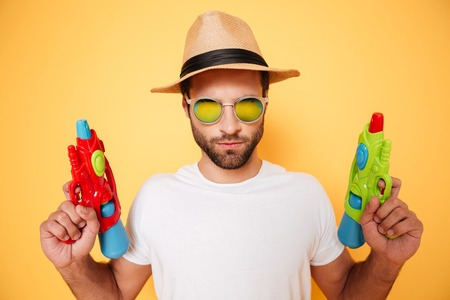 Photo of serious young man standing isolated over yellow background. Looking at camera holding toy water guns.