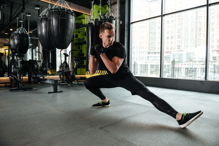 Image of handsome serious young sportsman make stretching exercises in gym. Looking aside.