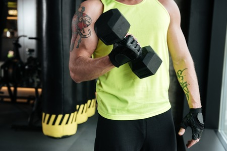 Cropped image of a young muscular sportsman lifting dumbbell at the gym