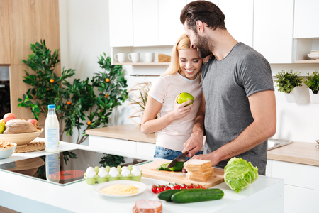 Picture of smiling young loving couple standing at kitchen and cooking together. Looking aside. Imagens
