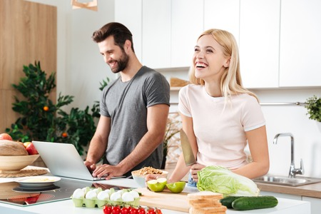Smiling couple using notebook to cook in their kitchen and laughing Stock Photo