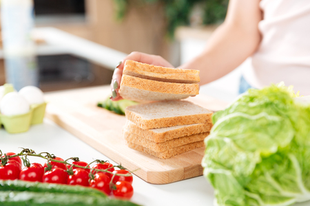 Close up portrait of a woman making sandwiches with vegetables on a cutting board