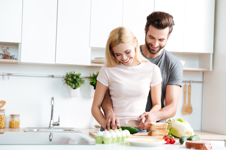 Beautiful smiling couple cooking together in a modern kitchen at home 写真素材