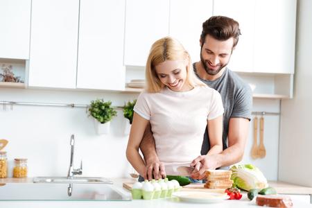 自宅でモダンなキッチンで一緒に調理美しい笑顔のカップル