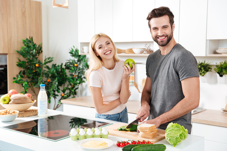Smiling couple spending time together in the kitchen at home Stockfoto