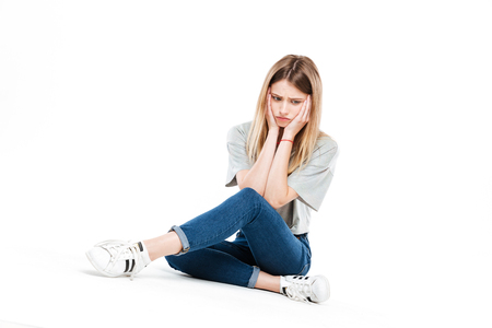 Pensive upset blonde young woman sitting cross-legged on floor and looking aside isolated over white Stock Photo