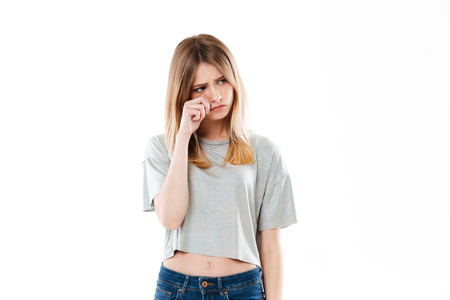Portrait of an upset girl crying and looking away isolated over white background Imagens