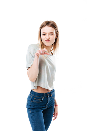 Portrait of a young casual girl making cat claw gesture isolated over white background Imagens