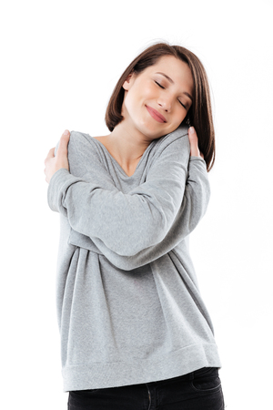 Portrait of a pretty young girl hugging herself with eyes closed while standing isolated over white background Stock Photo