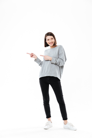 Full length portrait of a casual woman pointing two fingers away at copy space isolated over white background
