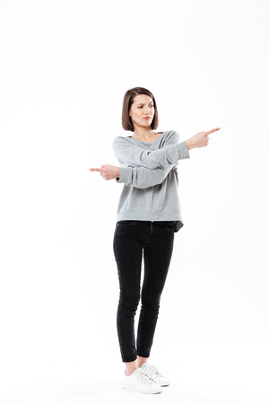 Full length portrait of a frustrated young girl pointing fingers both ways isolated over white background