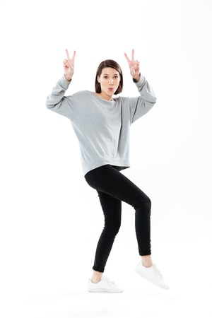 Full length portrait of a young casual woman posing and showing peace gesture isolated over white background Reklamní fotografie