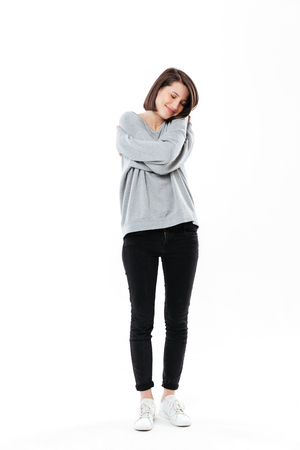 Full length portrait of a pretty young girl embracing herself while standing isolated over white background Stock Photo