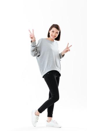 Full length portrait of a happy young woman standing and showing peace gesture with two hands isolated over white background Reklamní fotografie