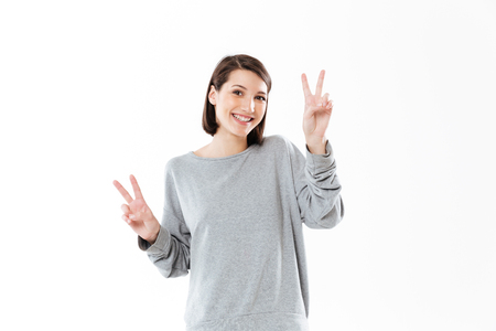 Portrait of a smiling happy woman showing peace gesture with two hands isolated over white background