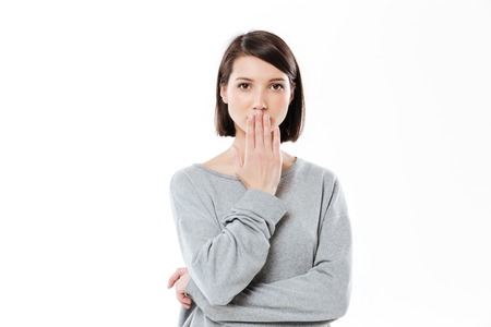 Portrait of a surprised young girl covering her mouth with hand isolated over white background