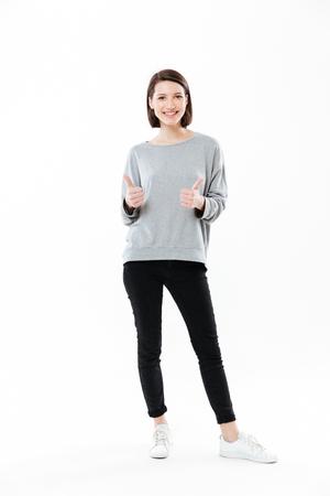 立っていると白い背景に分離された 2 つの手ジェスチャー親指を示す幸せな笑みを浮かべて少女の完全な長さの肖像画