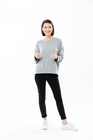 Full length portrait of a happy smiling girl standing and showing thumbs up gesture with two hands isolated over white background