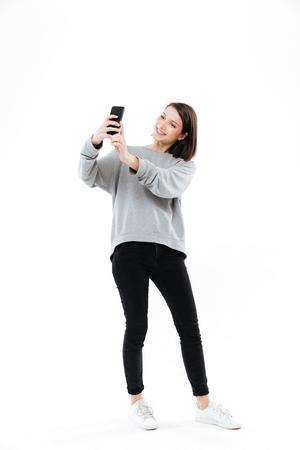Full length portret van een lachende mooie meisje staande en nemen selfie op mobiele telefoon geïsoleerd op witte achtergrond