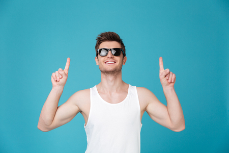 Cheerful young guy in sunglasses pointing isolated over blue background. Looking aside.
