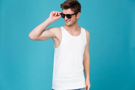 青い背景に分離されたポーズのサングラスの若い男のイメージ。よそ見。