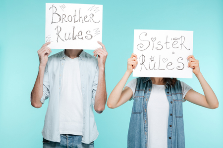 Picture of brother and sister holding funny nameplates over blue background.