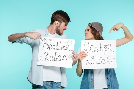 Young handsome brother and pretty sister holding funny nameplates over blue background. Looking aside. 版權商用圖片