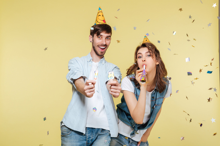 Image of happy brother and sister standing over yellow background. Looking camera. 版權商用圖片